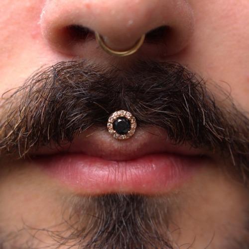 homem com piercing preto e dourado no bigode