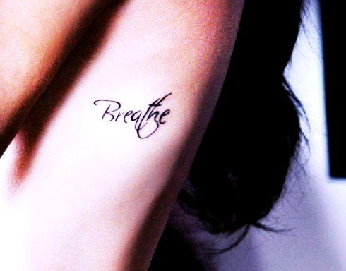 tatuagem feminina na costela breathe