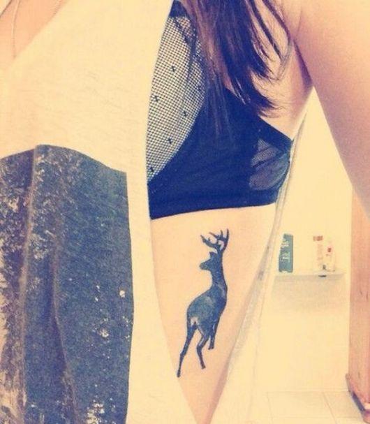 tatuagem feminina na costela cervo