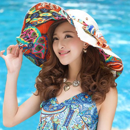 Menina com chapéu floppy colorido na praia.