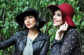 Mulheres de chapéu floppy em meio à folhagens.