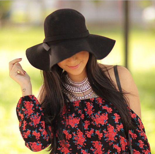 Mulher de vestido floral e chapéu