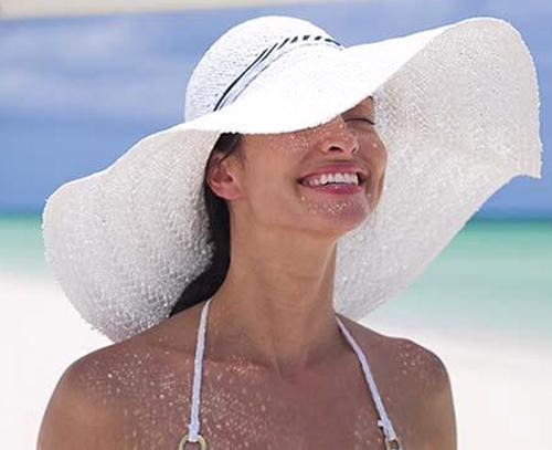 Mulher usando floppy na praia.