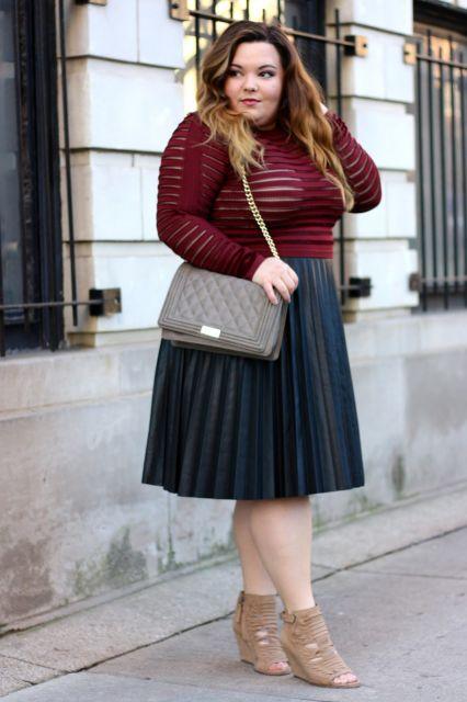 Modelo plus size usando saia plissada preta e blusa justa com transparência.