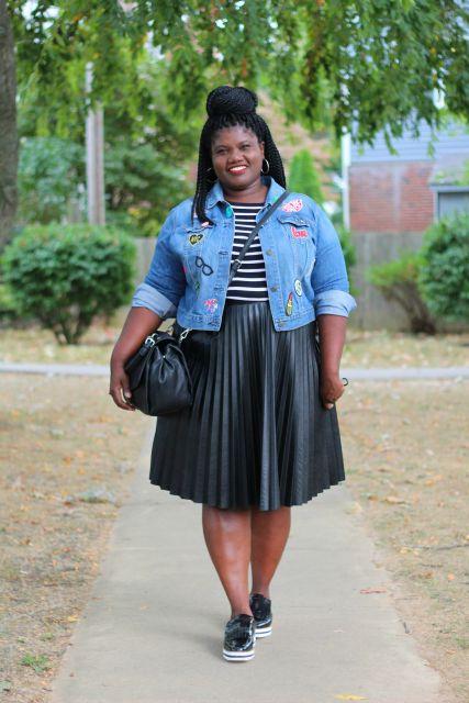 Mulher gordinha negra com saia preta, blusa listrada e jaqueta jeans.