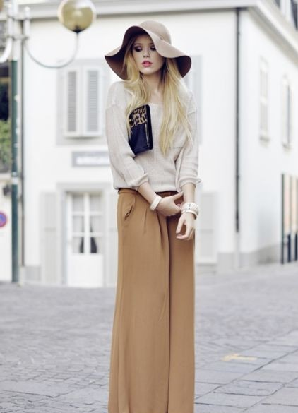 Mulher vestida de pantalona usando chapéu floppy.