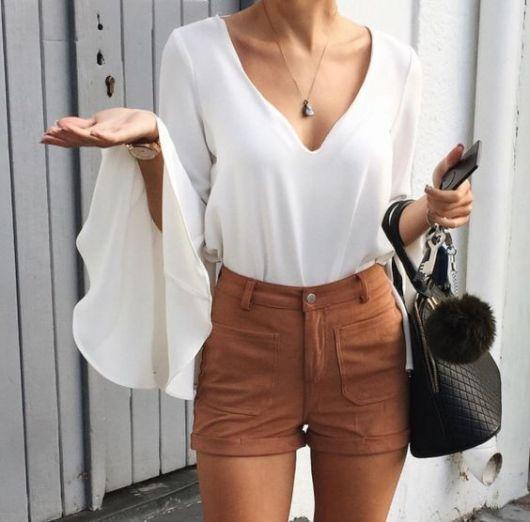 Mulher com camisa branca e shorts de camurça bege
