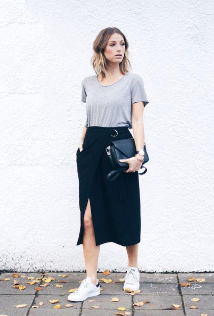 Mulher com saia longa preta e camiseta cinza