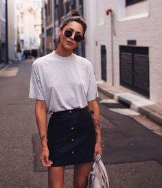 Mulher com saia preta curta e camiseta branca