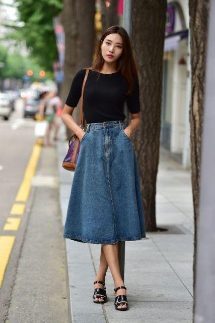 Mulher com saia longa jeans e camiseta preta