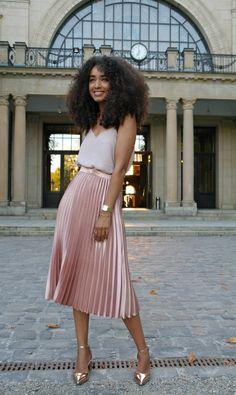 Mulher com saia plissada rosa e blusa branca