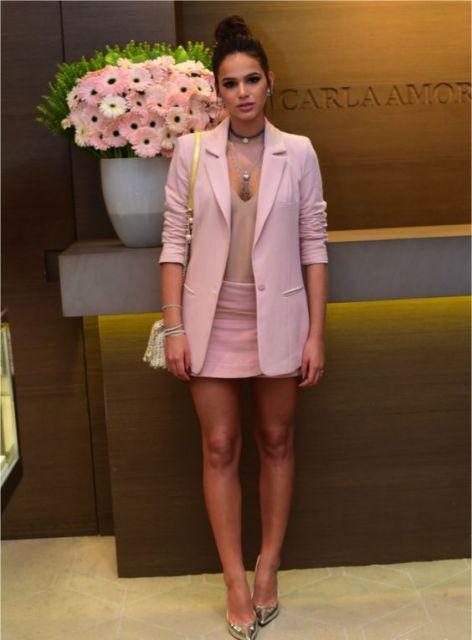 Mulher com saia, blusa e blazer em rosa claro