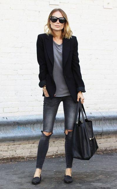 Mulher com calça jeans escura, camiseta cinza e blazer preto