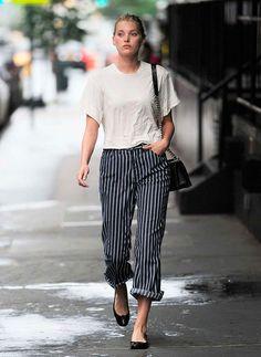 Mulher com calça larga listrada e camiseta branca