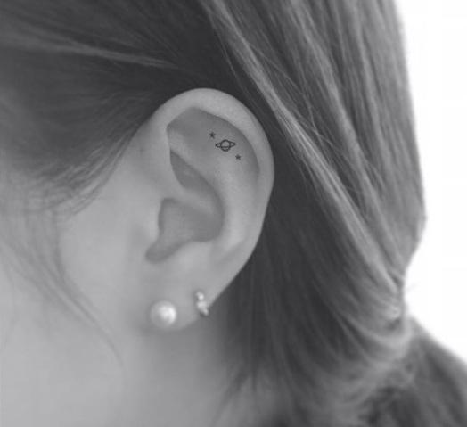Tatuagem pequena de planeta na orelha
