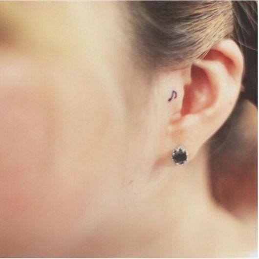 tatuagem de uma nota musical na orelha