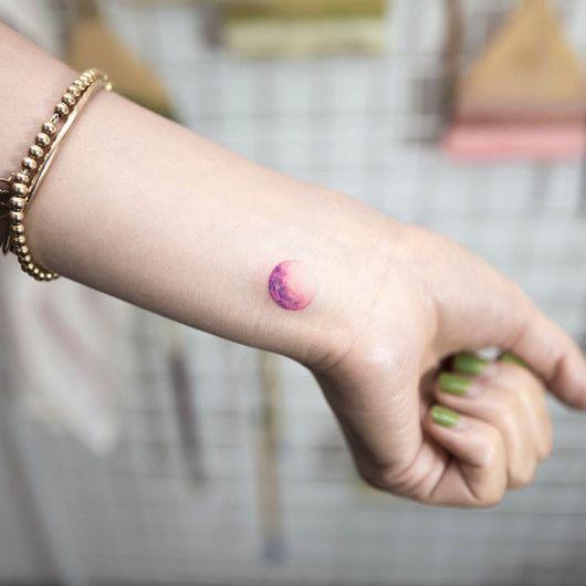 Tatuagem pequena da lua colorida no pulso
