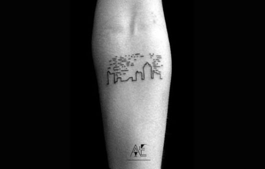 tatuagem de silhueta de cidade no braço