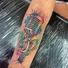 Tatuagem com as cores rosa, azul, verde e amarelo.