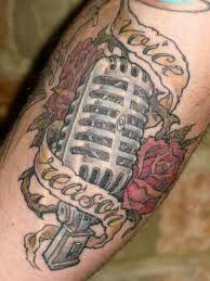 Tatuagem de microfone com frase.