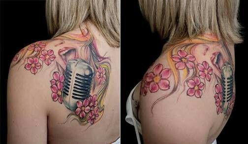 Tatuagem com rosto de uma mulher cantando em um microfone com várias flores ao redor.