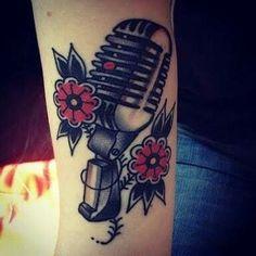Tatuagem de microfone com duas flores.