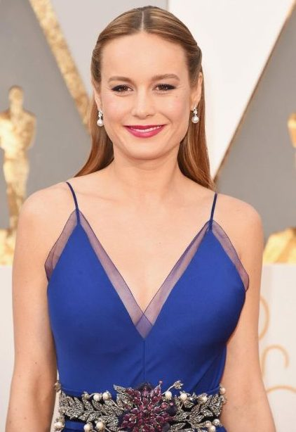 Brie Larson usando vestido azul e brinco de pérolas