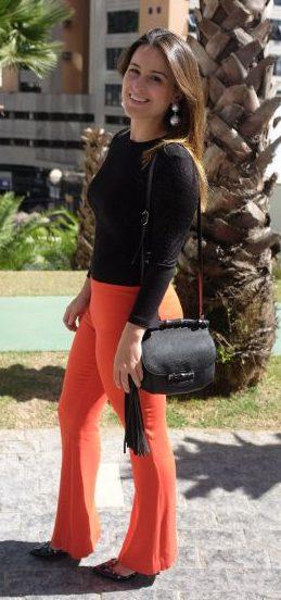 Mulher usando blusa preta, calça laranja e brinco maxi pérola