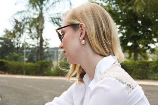 Mulher usando camisa branca e brinco de pérola inspirado em modelo Dior