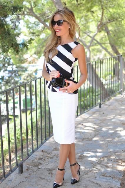 Mulher vestindo blusa de listras preto e branco e saia branca