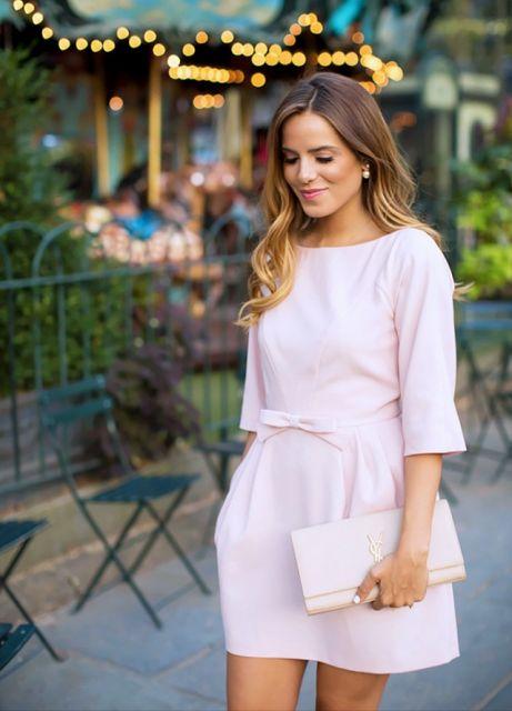 Mulher usando vestido rosa bebê com laço
