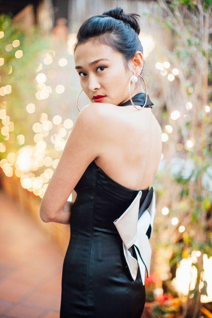Mulher usando vestido preto com detalhes brancos em origami