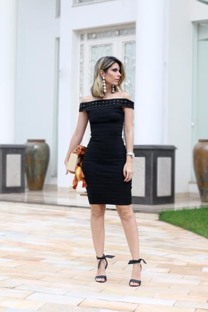 Mulher usando vestido preto de crochê e Maxi brincos de pérola
