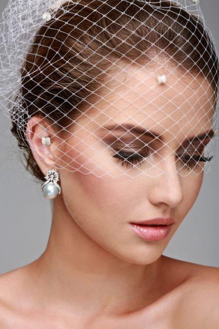 Noiva usando casquete e brinco de pérola com cristais