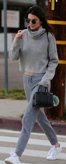 Kendall Jenner veste blusa cinza gola rolê, calça moletom cinza, tênis branco e bolsa preta pequena de mão.