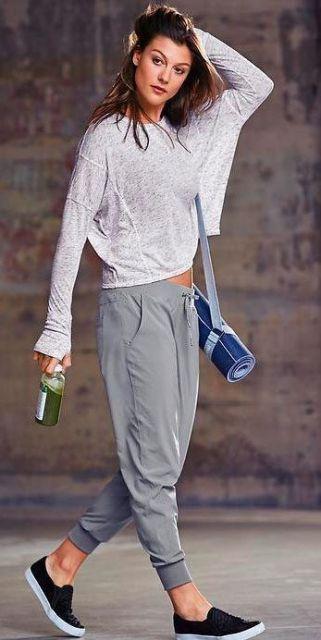Modelo veste blusa fluída branca, calça moletom cinza e sapatilha preta com sola branca.