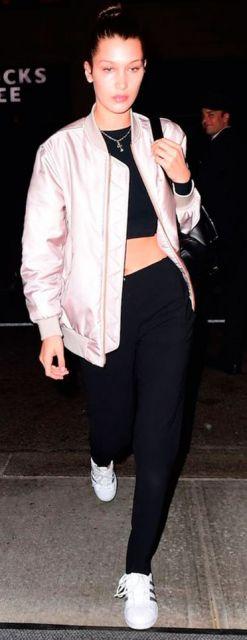 Bella Hadid veste calça moletom preta com blusa no mesmo tom, tênis branco e jaqueta cintilante rosa bebe.