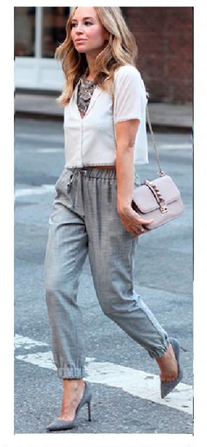 Modelo veste calça moletom cinza, sapato scarpin no mesmo tom e blusa cropped cinza claro com bolsa de ombro na cor rosê.