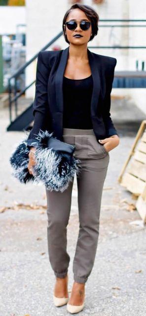 Look com calça moletom cinza escuro, blusa preta, blazer azul marinho, bolsa de mão de plumas e sapato nude.