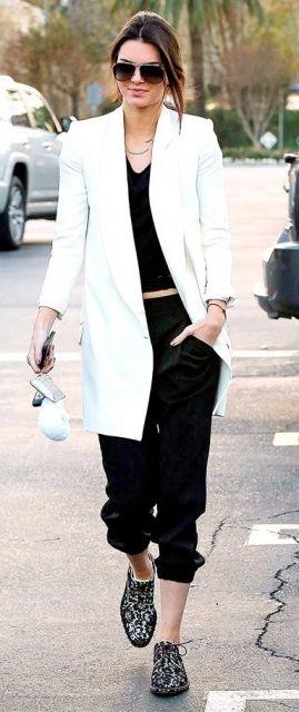 Kendal Jenner veste calça moletom preta, blusa no mesmo tom, sapato com brilhos.e blazer longo branco.