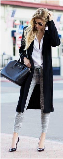 Modelo veste calça moletom cinza, camisa branca, sapato salto fino preto e casaco longo com bolsa no mesmo tom.