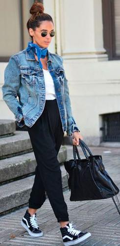 Modelo veste calça moletom preta, camisetinha branca, jaqueta jeans, tênis all star e bolsa preta.