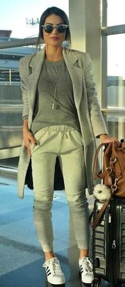 Camila Coelho veste calça moletom, blusa e casaco longo no tom cinza e tênis branco.