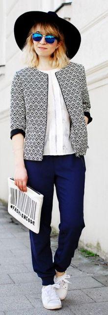 Look com calça moletom azul, blusa branca, blazer estampado e chapéu.