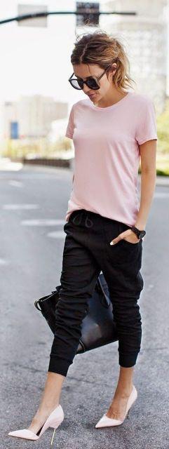 Modelo veste camisetinha rosa, calça moletom preta, sapato fechado salto fino da mesma cor da blusa.