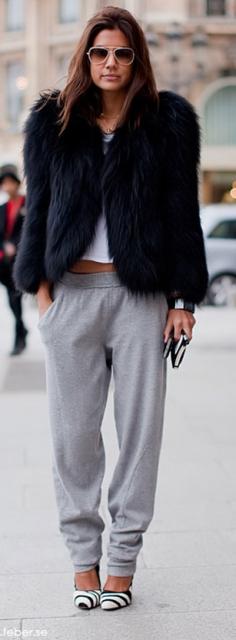 Modelo veste calça moletom cinza, com casaco de pele preto e sapato estampado.