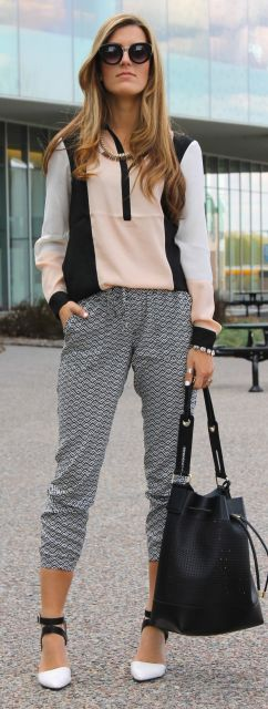Modelo veste calça moletom cinza, blusa mesclada nas cores rosa, preto e branco e sapato com amarrações.