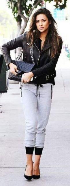 Modelo veste calça moletom cinza, sapato e jaqueta de coro em tons de preto.