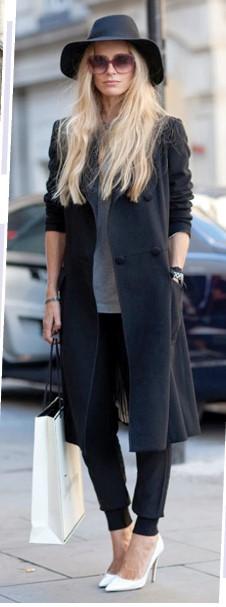 Modelo veste calça moletom preta, sapato, sobre-tudo preto e chapéu.