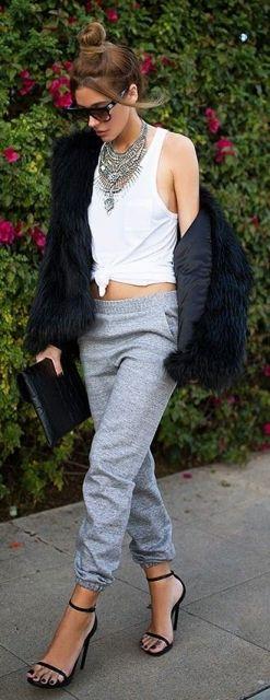 Modelo veste calça cinza, sandália preta, regatinha branca e casaco de pele.